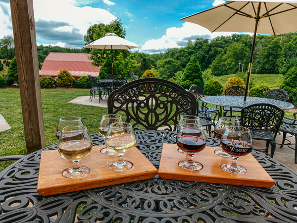 Linville Falls Winery NC two wine flights with red and white wines on table looking out over green grass
