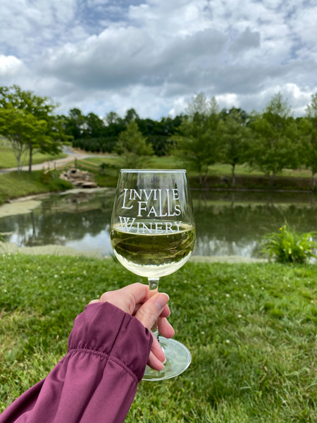 Linville Falls Winery with white hand in purple shirt raising white wine glass in front of pond