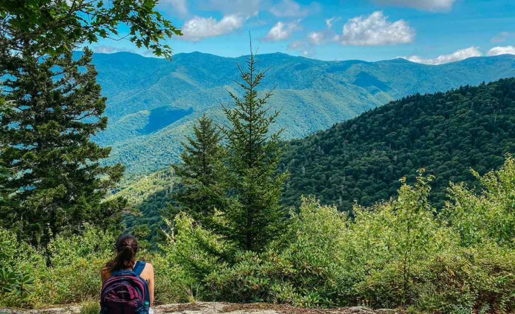 Little Butt Big Butt Trail NC with white brunette woman sitting on a rock with backpack looking out at the Black Mountains with trees and clouds in sky