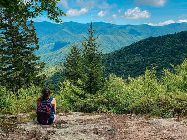 Little Butt Big Butt Trail Overlook with white brunette woman sitting on a rock with backpack looking out at the Black Mountains with trees and clouds in sky
