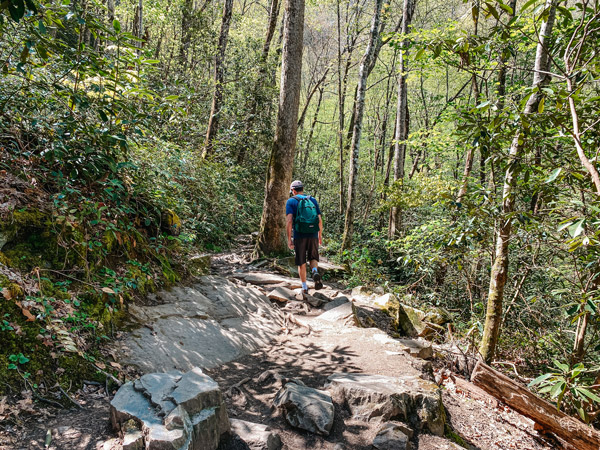 Mingo Falls Pigeon Creek Trail NC with white brunette male wearing green backpack hiking along rocks in forest