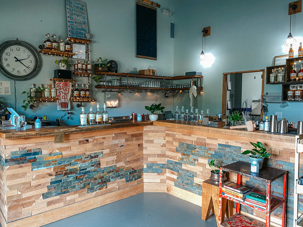 Oak And Grist Distilling Company Bar Black Mountain NC with clock, gin and whiskey bottles and glassware