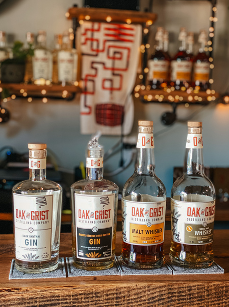 Oak and Grist Distilling Company Black Mountain NC with four bottles of whiskey and gin on a bar