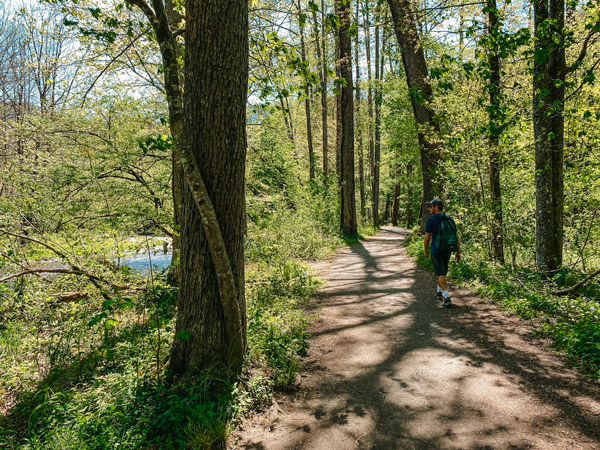 Oconaluftee River Trail Great Smoky Mountains National Park with white brunette male wearing hat and green backpack walking down dirt trail by the river