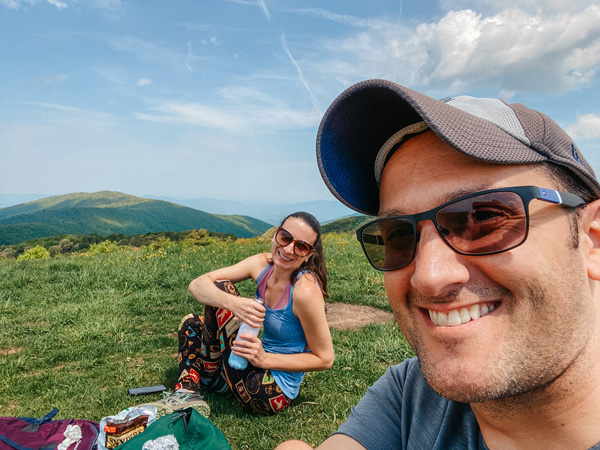 Best things to do near Asheville like Picnic On Max Patch Summit with brunette white male and female hikers sitting on the ground with lunch
