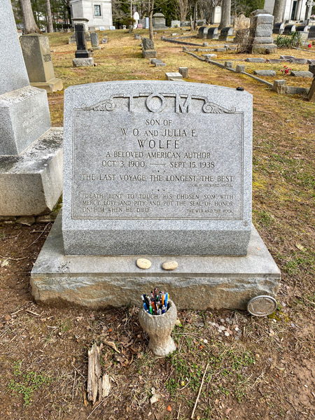 Thomas Wolfe Gravestone at Riverside Cemetery in Asheville NC with vase filled with pens and green grass