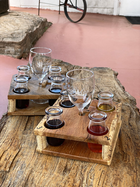 Wine Flight Baker Buffalo Creek Vineyard and Winery with four small glass milk bottles filled with wine and wine glass in middle of flight on wooden tree table