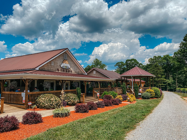 Woodmill Winery NC one story tasting room with gravel road, vineyards, and tables out front