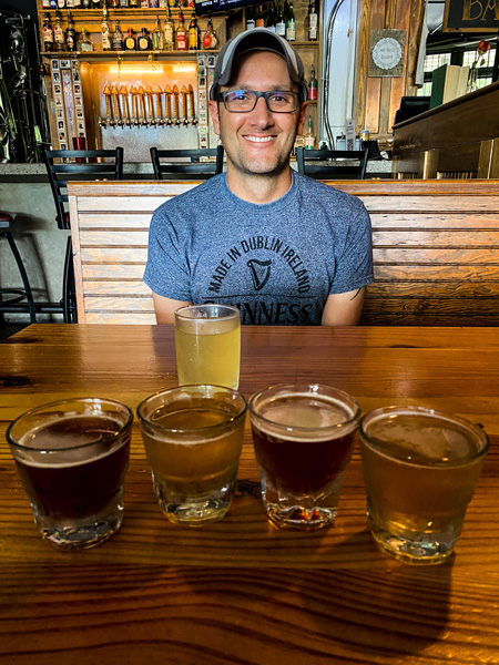 All Sevens Brewing Asheville NC with white  brunette male in blue t-shirt with 5 flight glasses filled with various amber and blonde beers