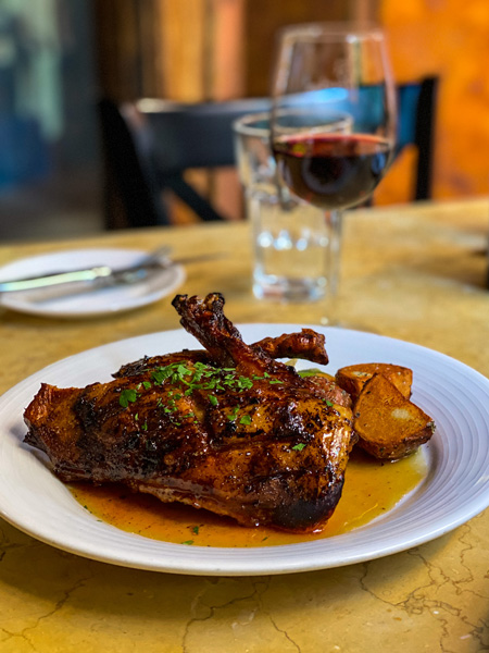 Best Asheville Restaurants Bouchon with roasted duck on plate with sauce and glass of water and red wine