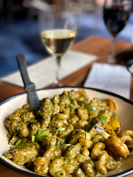 Best Restaurants In Asheville Nine Mile Montford with bowl of pasta with dairy free pesto, shrimp, veggies, and glass of white wine