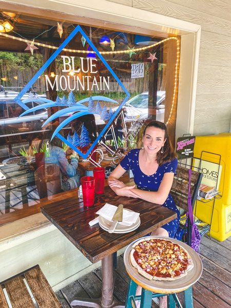 Blue Mountain Pizza Weaverville NC with white brunette woman in a blue dress sitting with a pizza in front of the restaurant