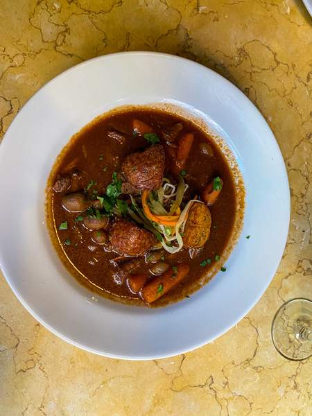 Bouchon Restaurant Asheville North Carolina with bowl of beef stew with carrots, potatoes, and mushrooms