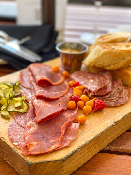Charcuterie The Great Hall Bar Grove Park Inn with three different types of meats, pickles, bread, and red and orange peppers