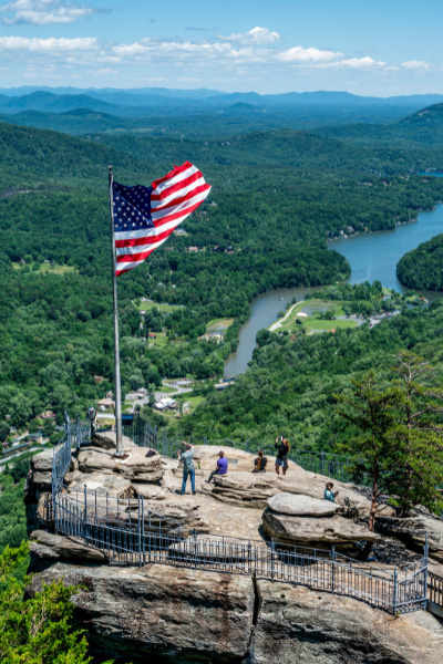 Chimney Rock State Park with rock, view of Lake Lure, and American flag blowing in the breeze
