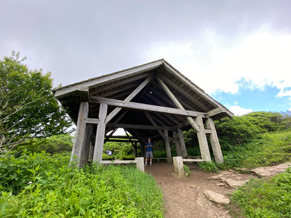 Craggy Gardens Trail Shelter with white brunette male under an open but covered wooden structure