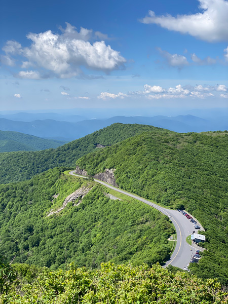 Craggy Pinnacle Blue Ridge Parkway NC in the summer with green grass, view oof Craggy Gardens Visitor Center parking lot, BRP road, and mountains around Craggy Gardens with blue sky and clouds