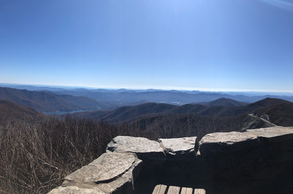 Craggy Pinnacle Trail Blue Ridge Parkway NC with benches, stone wall, and view of Blue Ridge Mountains and Asheville reservoir