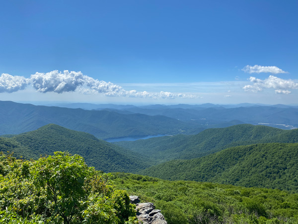 Craggy Pinnacle Trail Hike NC with view of Asheville watershed along green grass Blue Ridge Mountains