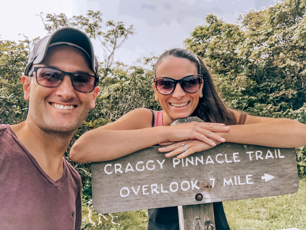 Craggy Pinnacle Trailhead with white brunette male and female with sunglasses in hiking clothes at trailhead sign that says Craggy Pinnacle Trail overlook .7 mile