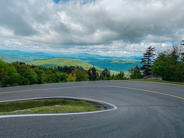 Forrest Gump Curve Grandfather Mountain with blue and green mountains in the distance behind curved paved road