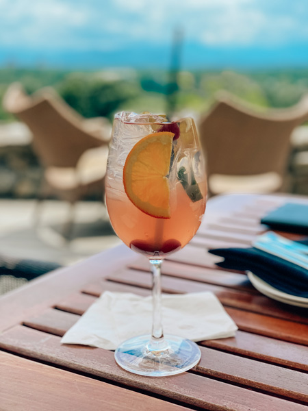 The Great Hall Bar Omni Grove Park Inn Asheville, NC white sangria cocktail with fruit garnish and blur of Blue Ridge Mountains and downtown Asheville in the background
