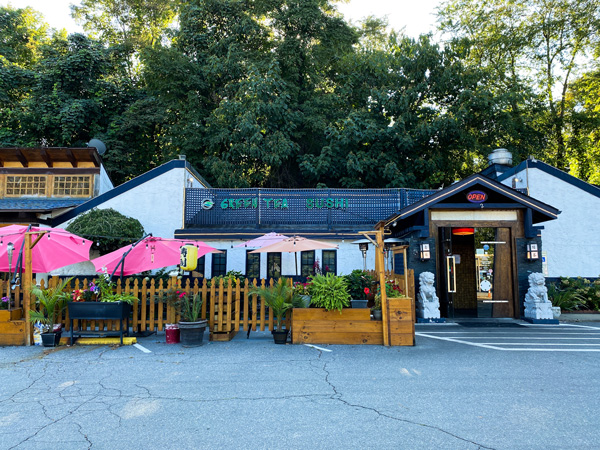 Green Tea Sushi Restaurant Asheville NC with picture of building and parking lot with patio and tables with red umbrellas