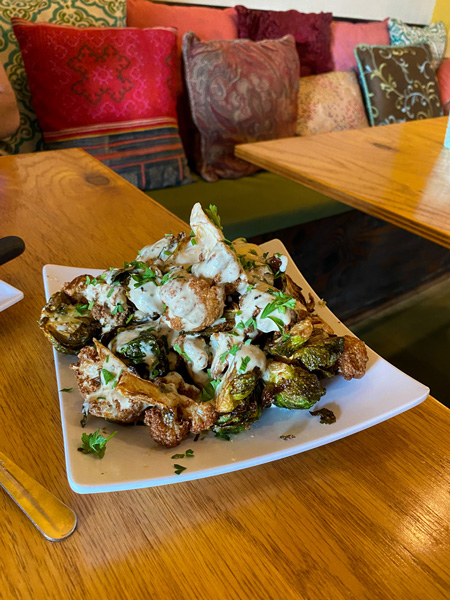 Gypsy Queen Cuisine Best Vegan and Gluten-free Restaurant Asheville NC with plate of mixed fried cauliflower and Brussel sprouts