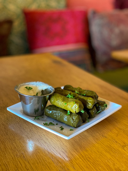 Gypsy Queen Cuisine Vegan Restaurant Asheville NC with plate of pile of grape leaves and dipping sauce