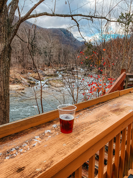 Hickory Nut Gorge Brewery with amber beer in plastic cup on ledge in front of river