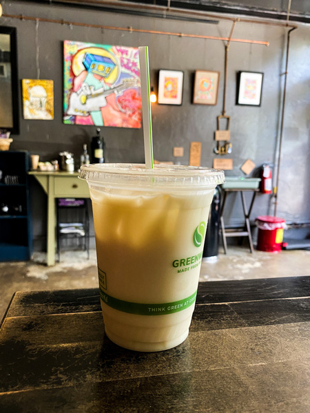 Izzys Coffee Asheville NC with iced coffee on table with art in background