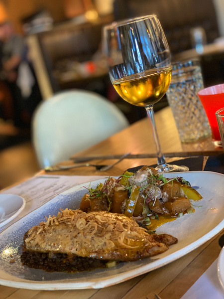 Jargon Restaurant Asheville NC with plate of meat, veggies, and glass of white wine on table