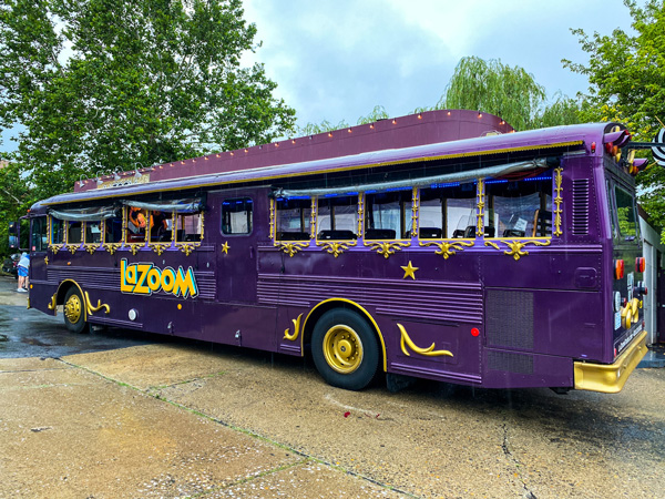 LaZoom Comedy Bus Tours Asheville NC purple bus with open windows and yellow trim