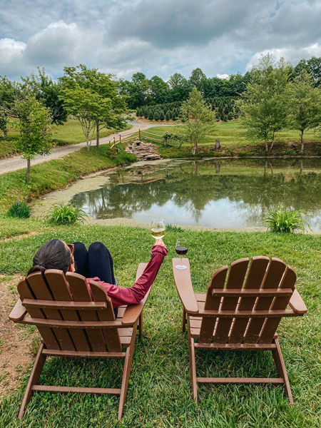 Linville Falls Winery with white brunette woman sitting in chair in front of vineyards and pond with glass of white wine