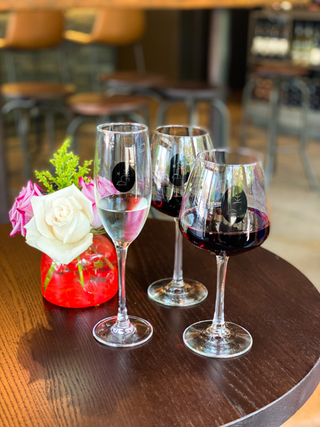 Marked Tree Vineyard Wine Bar Asheville NC with two red glasses of wine and Champagne flute with vase of flowers on table