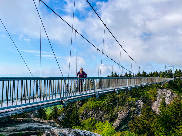 Mile High Swinging Bridge Grandfather Mountain with white brunette woman in middle of a walking bridge