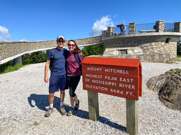Mount Mitchell Blue Ridge Parkway NC with white brunette male and female standing in front of sign that says highest peak east of the Mississippi River elevation 6684 feet with stone viewing platform behind them