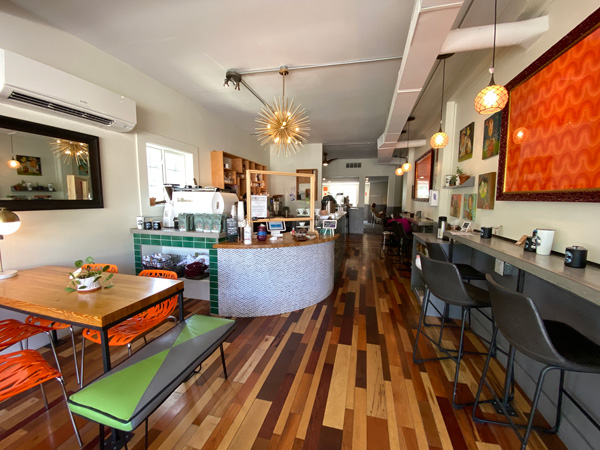 PennyCup Coffee Co Asheville NC with green, black, and orange benches and chairs, bar, fancy  light, and orange picture