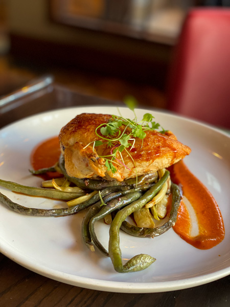 Posana Gluten Free restaurant downtown Asheville with roasted chicken and string beans with red sauce on plate