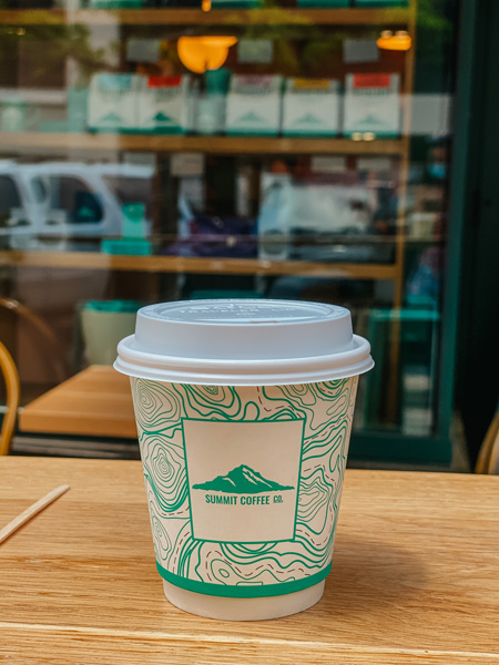 Summit Coffee Co Downtown Asheville with to-go coffee cup with lid in front of coffeeshop storefront