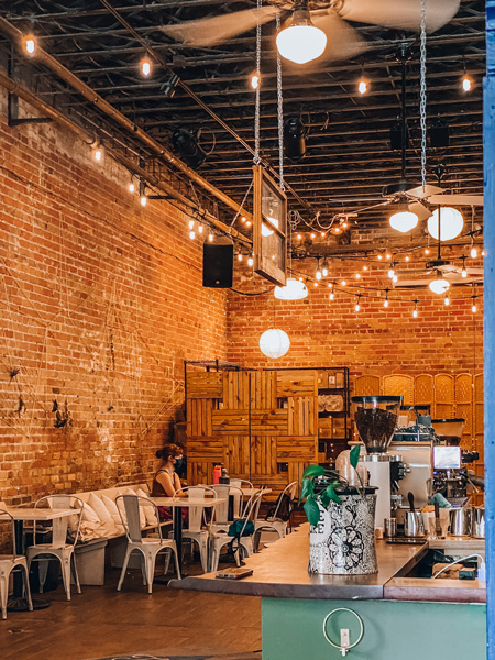 Trade and Lore Coffee Downtown Asheville NC with tall ceilings, hanging lights, tables, chairs, and coffee bar