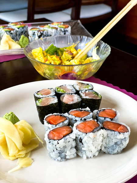 Umi Sushi Near Asheville with picture of yellow tail and salmon sushi rolls with ginger salad with chopsticks