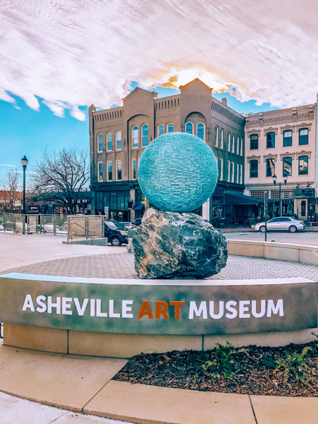 Asheville Art Museum blue ball sculpture with downtown and sunset in the background