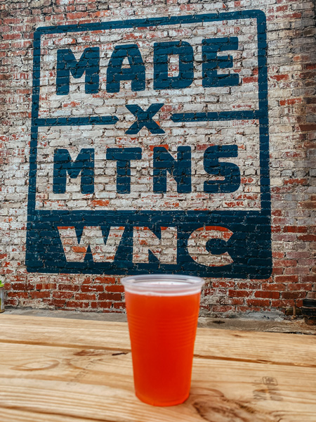 Beer and Gear Black Mountain NC with picture of amber beer in plastic cup in front of mural on brick wall that says Made x Mnts WNC
