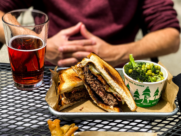 Black Mountain Kitchen and Ale House Burgers with glass filled with red cider and burger on gluten free bread with southern sides