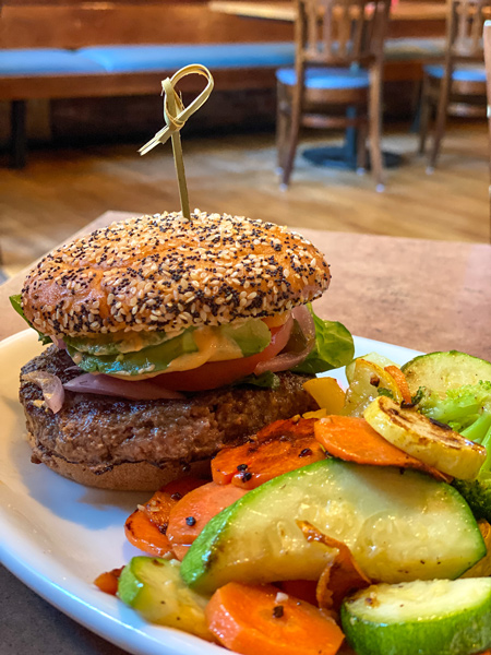Burger from Twisted Laurel Weaverville on gluten-free bun with side of veggies like carrots and zucchini