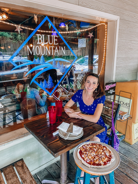 Gluten free Blue Mountain Pizza Weaverville NC with white brunette woman in blue bird dress sitting next to a gluten-free pizza and eating outside with Blue Mountain Pizza logo in background