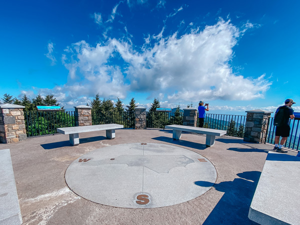 Mount Mitchell Summit Blue Ridge Parkway NC from viewing platform with compass on ground and view of mountains, blue sky, and white clouds