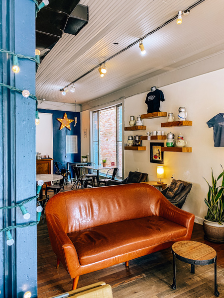The Dripolator Coffeehouse Black Mountain NC with brown couch, hanging yellow lights, shelves lined with knick knacks, and blue wall with a star