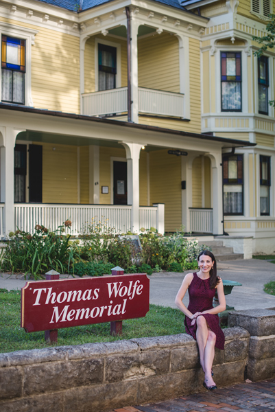Thomas Wolfe Memorial Asheville Museums with brunette white woman in maroon dress sitting in front of yellow boarding house